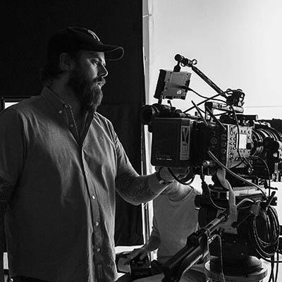 Director Jason Whitbeck adjusts a camera during video shoot