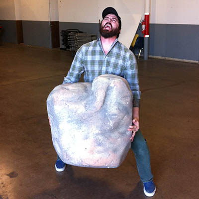 Director Jason Whitbeck lifts an enormous boulder