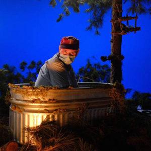 Director Joe Harris in metal bathtub with pine trees