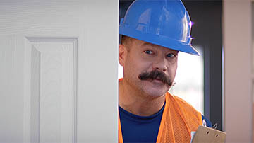 A construction worker peeks around a door