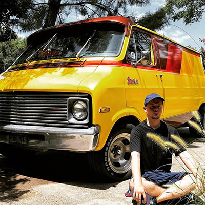 Rob Rigdon sitting in front of a sweet 70's van