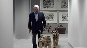 A dapper man in a suit walks down an elegant hallway with his dogs beside him